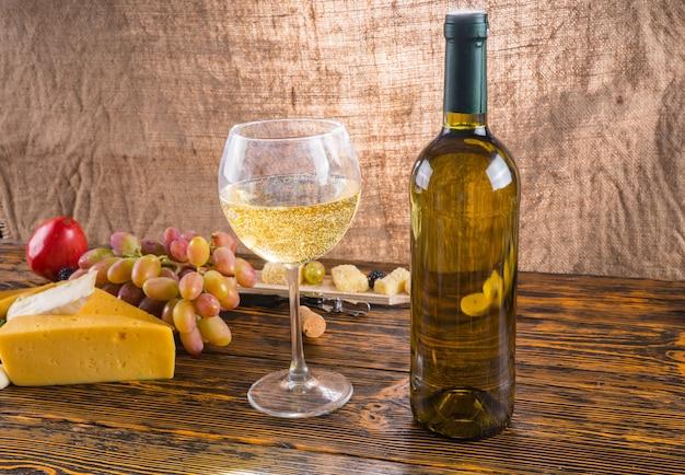 Martwa natura dla smakoszy - zbliżenie białego wina w szkle obok butelki na rustykalnym drewnianym stole z serem i winogronami