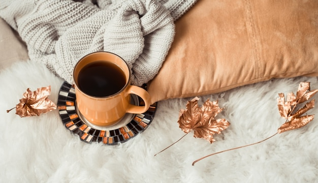 Martwa natura filiżanka herbaty z jesiennymi liśćmi i swetrem.