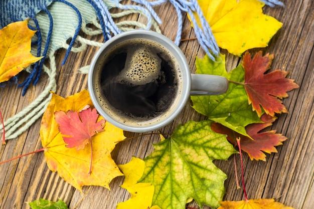 Martwa natura filiżanka kawy i jesienne liście w kratę