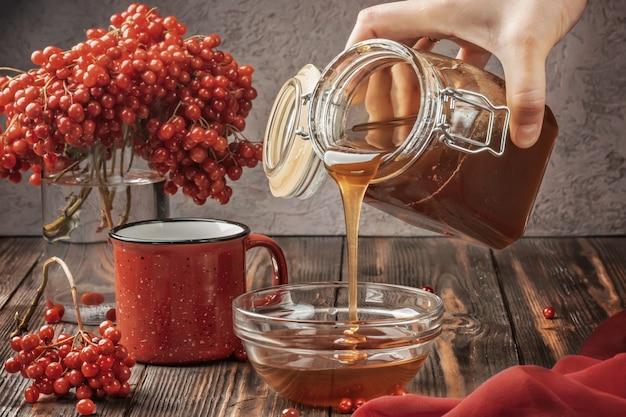 Martwa natura jagody kaliny w szklance i kubek gorącej herbaty i miodu