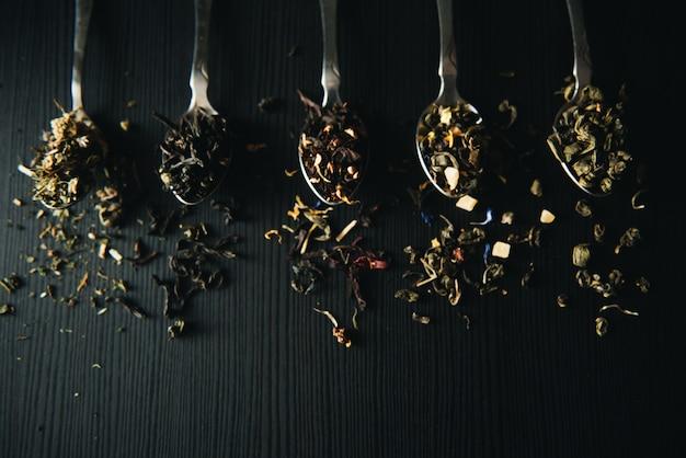 Martwa natura, jedzenie i picie koncepcja. różne rodzaje herbaty w łyżce na czarnej desce. selektywne ustawianie ostrości, kopia przestrzeń, ściana