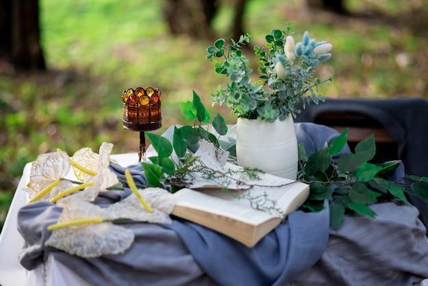 Martwa natura książka leży na stole obok wazonu