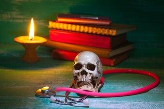 Martwa natura ludzka czaszka na stetoskop i stare książki z