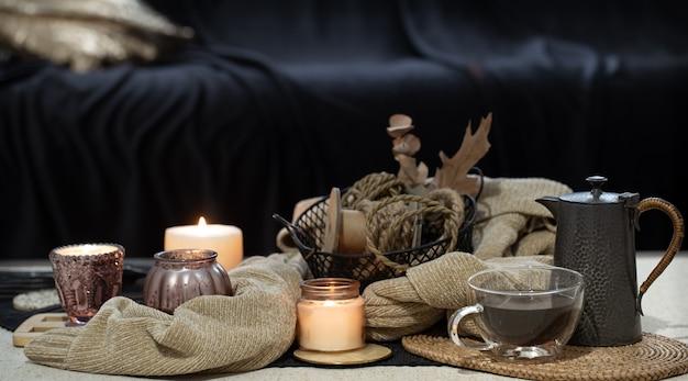 Martwa natura na stole ze świecami, książką sweter i jesiennymi liśćmi. przytulny salon, wystrój wnętrz domu.