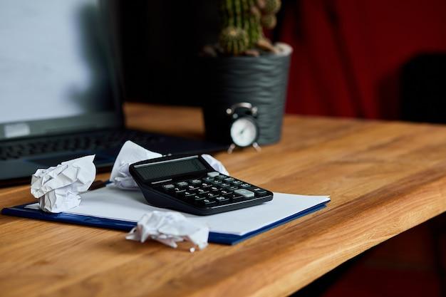 Martwa natura obszaru roboczego księgowego z kalkulatorem akcesoriów biurowych, kartką papieru, laptopem, notatnikiem, zmiętymi kulkami papierowymi, drewnianym stołem, usługami księgowymi i bankowymi. finanse i płatności