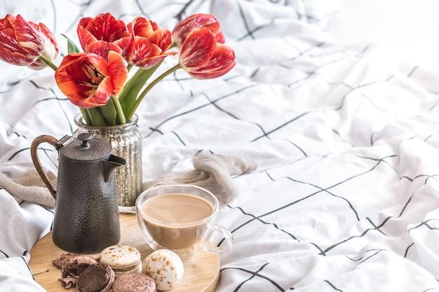 Martwa natura przytulna śniadanie z kawą i deserami makaroników. z pięknymi czerwonymi tulipanami w sypialni
