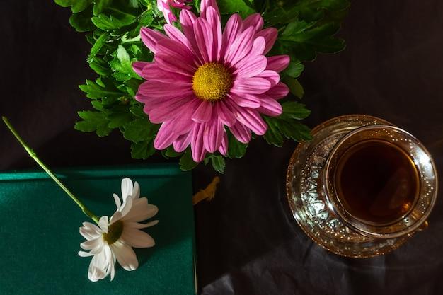 Martwa natura składająca się z filiżanki kawy, różowego kwiatu, książki