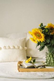 Martwa natura w domu wnętrza salonu. słoneczniki, kawa i otwarta książka. czytaj, odpoczywaj