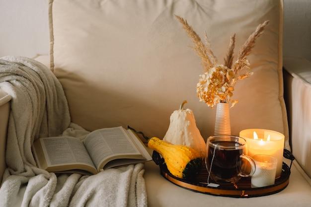 Martwa natura w mieszkaniu wnętrza salonu. dynia i filiżanka herbaty ze świecami na tacy porcji. odpoczynek i czytanie. przytulna jesień