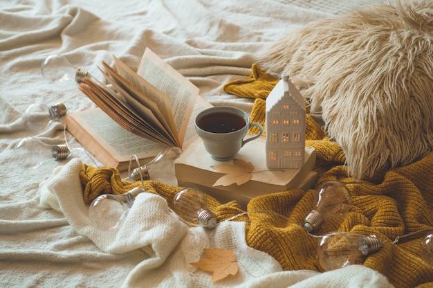 Martwa natura w mieszkaniu wnętrza salonu. swetry i filiżanka herbaty z domkiem ze świecami i jesiennym wystrojem na książkach. czytaj, odpoczywaj. przytulna koncepcja jesień lub zima.