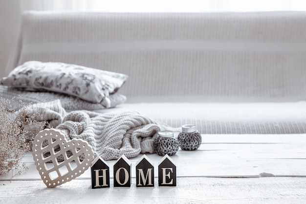 Martwa natura w stylu hygge z drewnianym słowem home, sercem i dzianiną. koncepcja domowego komfortu i nowoczesnego stylu.
