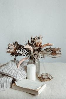 Martwa natura w stylu skandynawskim z bukietem kwiatów, dzianinowym elementem i ozdobnymi detalami