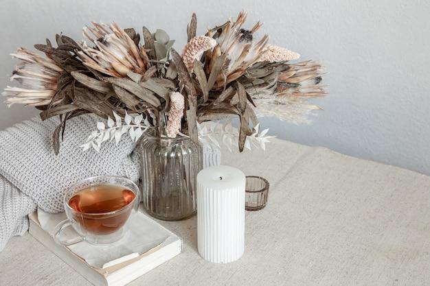 Martwa natura w stylu skandynawskim z filiżanką herbaty, dzianinowym elementem i miejscem na kopię książki
