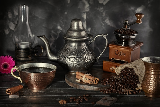 Martwa natura w stylu starej fotografii z młynkiem do kawy, ziaren kawy ze starą lampą i czajnikiem z filiżanką z parą