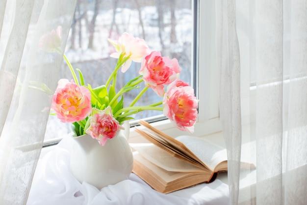 Martwa natura w wazonie z tulipanami i starą książką na oknie