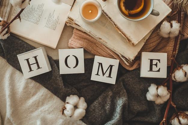 Martwa natura we wnętrzu domu oraz napis home. książki i filiżanka herbaty ze stożkiem i bawełną. czytaj, odpoczywaj. przytulna koncepcja jesień lub zima, dzianina. przytulna koncepcja jesień zima
