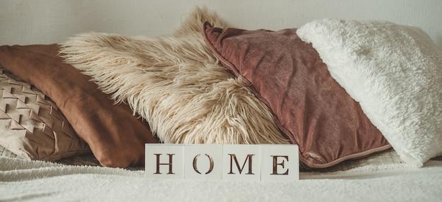 Martwa natura we wnętrzu domu oraz napis home. wiele ozdobnych przytulnych poduszek. odpoczynek. przytulna koncepcja jesień lub zima, dzianina. koncepcja domu