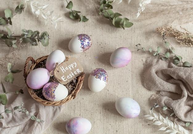 Martwa natura wielkanocna z jajkami ozdobionymi cekinami w wiklinowym koszu. wesołych świąt wielkanocnych koncepcja