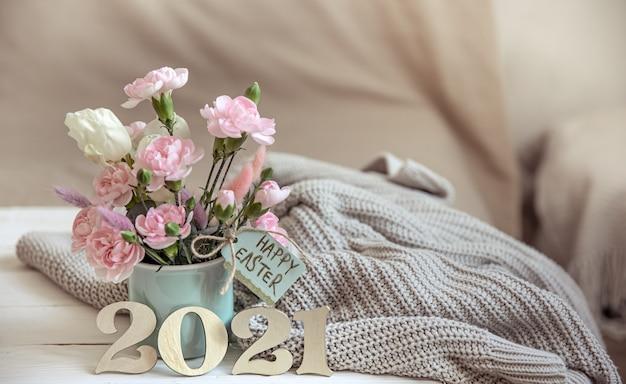 Martwa natura wielkanocna ze świeżymi wiosennymi kwiatami w wazonie, dziana z elementem i ozdobnym numerem roku 2021.