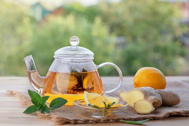 Martwa natura, wzmocnienie odporności i koncepcja opieki zdrowotnej. imbirowa herbata, cytryna i mennica na drewnianym stole. selektywne ustawianie ostrości.