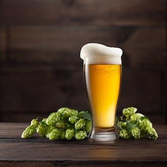 Martwa natura z beczką piwa i zielonym chmielem na ciemnobrązowym drewnianym stole
