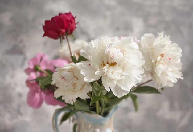 Martwa natura z biało-różowymi piwoniami w białym wazonie