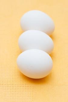 Martwa natura z białymi jajkami kurczaka na żółtym tle