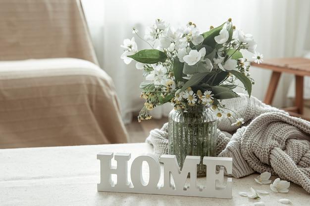 Martwa natura z bukietem kwiatów, książką i drewnianym ozdobnym słowem do domu.