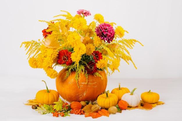 Martwa natura z bukietem kwiatów w pomarańczowej dyni na stole dekoracja na święto dziękczynienia