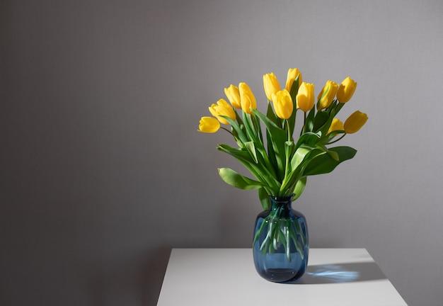Martwa natura z bukietem żółtych tulipanów w niebieskim szklanym wazonie na białym stole. wystrój wnętrz domu. skopiuj miejsce