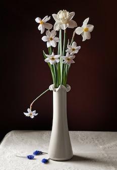 Martwa natura z bukietem żonkili w białym wazonie i rozrzuconych hiacyntów na okrągłym stole z białym obrusem.