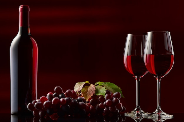 Martwa natura z butelką czerwonego wina, kieliszków i winogron. czarne i czerwone tło.
