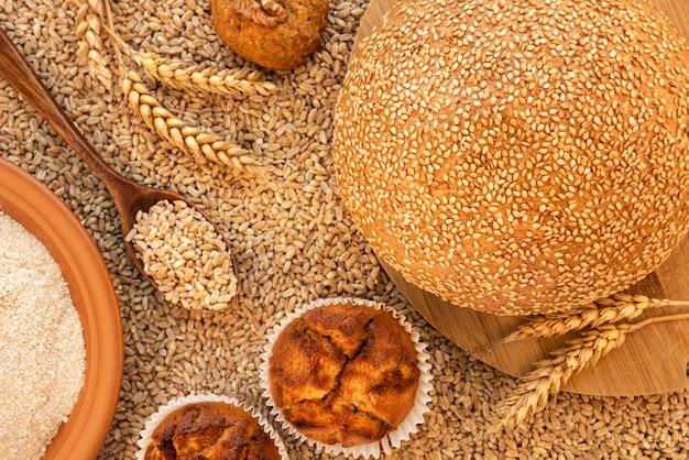 Martwa natura z chlebem, babeczkami, ciasteczkami, kłoskami, talerzem mąki orkiszowej i łyżką z ziarnami. znajduje się na tle rozsypanych ziaren spelty. widok z góry.