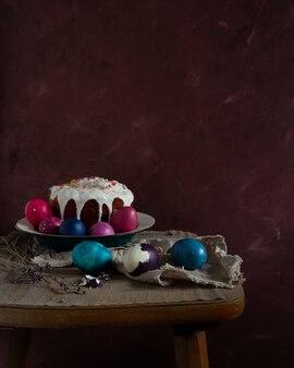 Martwa natura z ciastem wielkanocnym i kolorowymi jajkami na ciemnym stole rustykalnym