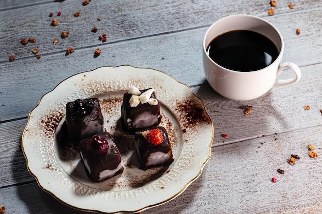 Martwa natura z deserem ciasto czekoladowe i filiżankę kawy na drewnianym stole
