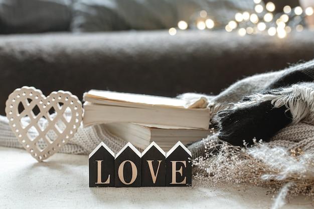 Martwa natura z drewnianymi słowami miłość, książkami i przytulnymi przedmiotami na niewyraźnym tle z boke.