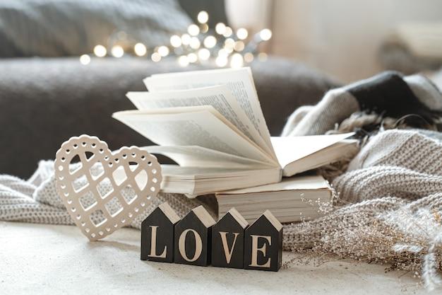 Martwa natura z drewnianymi słowami miłość, książkami i przytulnymi przedmiotami z boke.