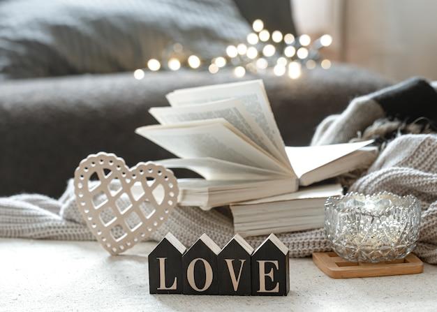 Martwa natura z drewnianymi słowami miłość, książkami i przytulnymi przedmiotami