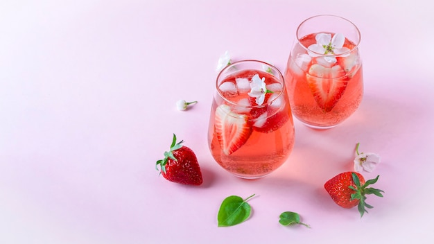 Martwa natura z dwiema szklankami chłodzącej sangrii truskawkowej z winem musującym, truskawką, kostkami lodu