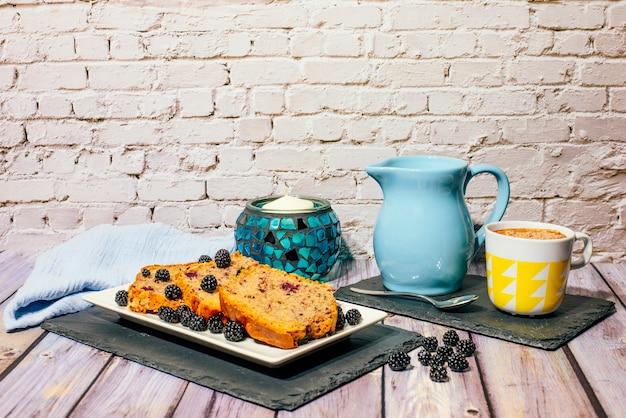 Martwa natura z dzikiego ciasta owocowego z filiżanką mleka z kakao i dzbanek na mleko.