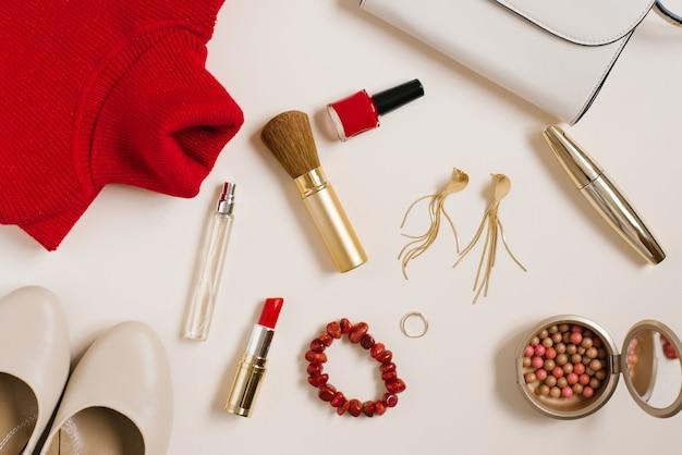 Martwa natura z fashionistką. powierzchnia kosmetyczna dla kobiet. kosmetyki i odzież w kolorze czerwonym