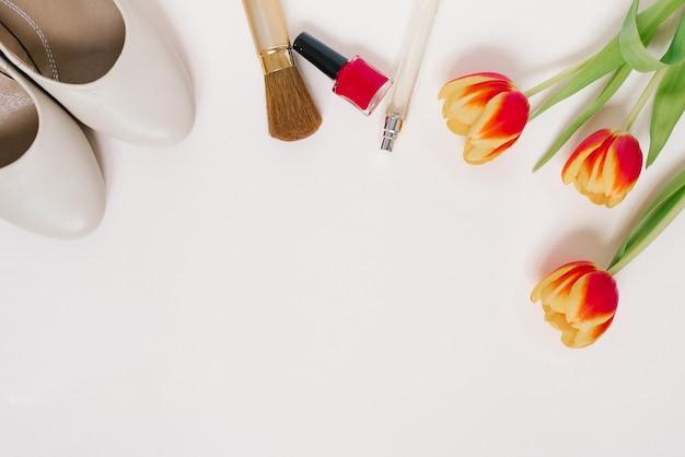 Martwa natura z fashionistką. tło kosmetyczne kobiet. stylowe dodatki, bukiet tulipanów i ubrania blogerki. kopiowanie spacji