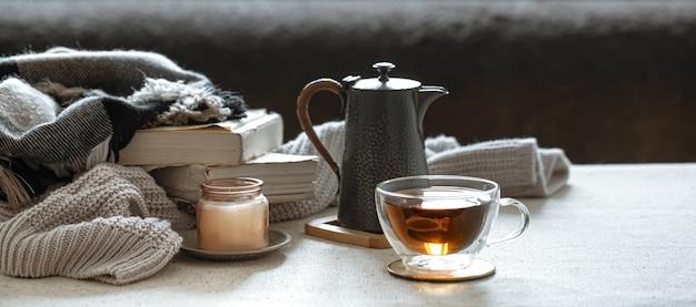 Martwa natura z filiżanką herbaty, czajnikiem, książkami i świeczką w świeczniku. koncepcja komfortu w domu.