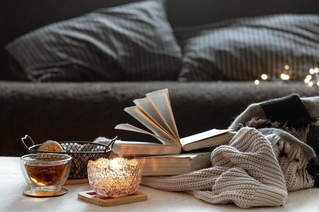 Martwa natura z filiżanką herbaty, książkami i płonącą świecą w pięknym świeczniku. koncepcja komfortu w domu.