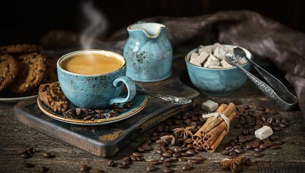 Martwa natura z filiżanką pachnącej gorącej kawy na drewnianym stole z bliska