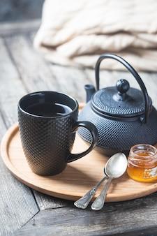 Martwa natura z filiżanki czarnej herbaty z dzbankiem na herbatę na tacy na drewnianym stole. czas na herbatę w przytulnej atmosferze