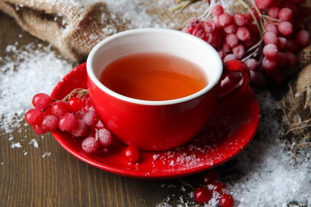 Martwa natura z herbatą kaliny w filiżance, jagodach i śniegu, na parcianej serwetce, na drewnianym tle