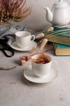 Martwa natura z herbatą wylewającą się z filiżanki, książek i kwiatów