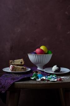 Martwa natura z kawałkami ciasta wielkanocnego, kolorowych jaj i skorupek jajek na rustykalnym stole