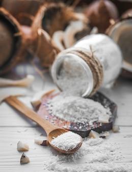 Martwa natura z kokosem i płatkami kokosowymi w drewnianych łyżkach i szklanym słoju na drewnianym tle